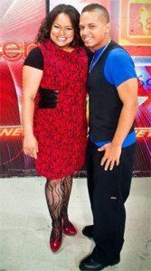 Jose posing with fan wearing red dress